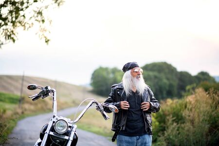 Senior man traveller with motorbike and sunglasses in countryside.