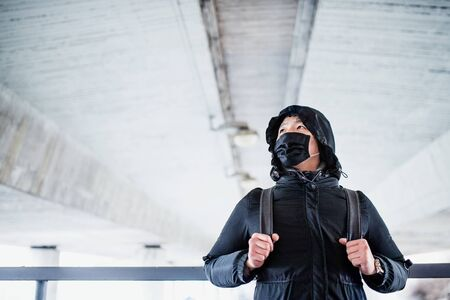 Man in black clothes and respirator standing outdoors in city, coronavirus concept. Stok Fotoğraf