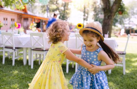 Small girls dancing outdoors in garden in summer, birthday celebration concept.