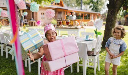 Portrait of small girl with presents outdoors in garden in summer. 版權商用圖片