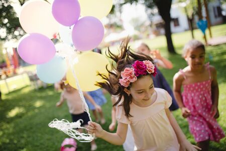 Small children running outdoors in garden in summer, playing.