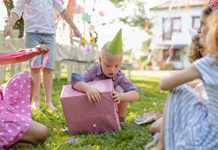 Down syndrome child with friends on birthday party outdoors, opening presents.