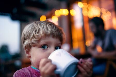 Close-up of toddler boy standing outdoors, drinking from cup. 版權商用圖片
