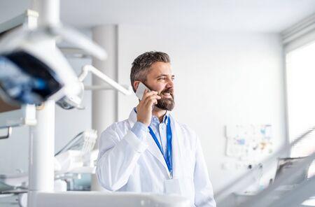 Mature dentist in modern dental surgery, using smartphone.