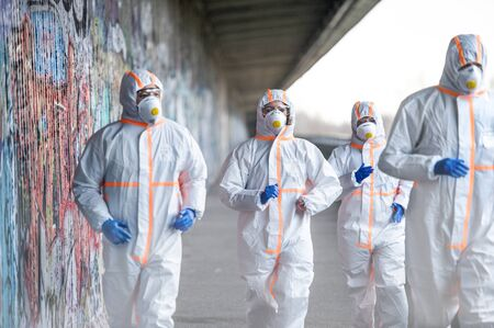 People with protective suits and respirators running outdoors, coronavirus concept.