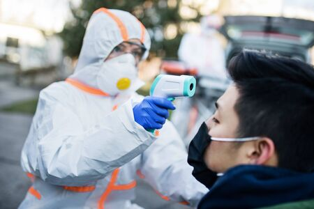 People with protective suits helping man outdoors, coronavirus concept.