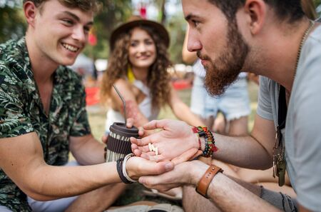 Group of young friends at summer festival, drug dealing concept. Stock fotó