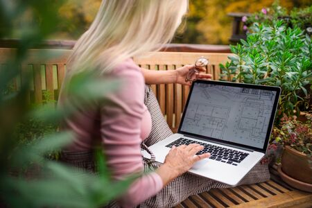 Senior woman architect with laptop sitting outdoors on terrace, working. Standard-Bild - 140469952