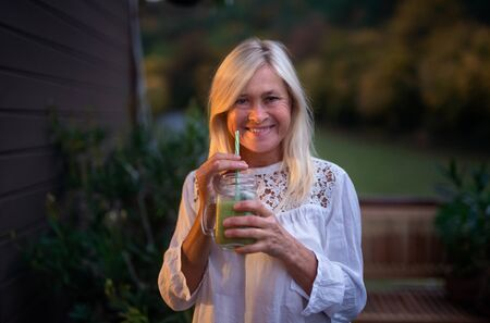 Senior woman with juice standing outdoors on terrace, looking at camera. Standard-Bild - 140470573