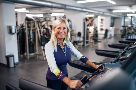 A senior woman in gym doing cardio work out exercise. Standard-Bild - 140470387