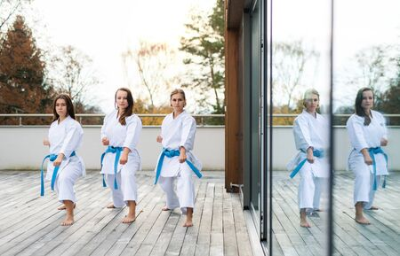Group of young women practising karate outdoors on terrace.