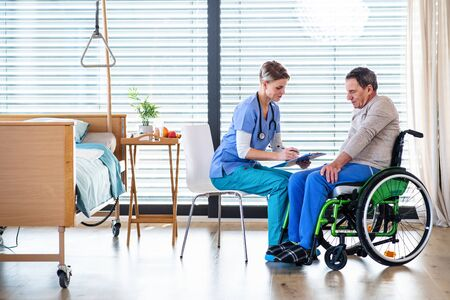 A healthcare worker and senior patient in wheelchair in hospital, talking.