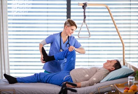 A healthcare worker and senior patient in hospital, physiotherapy. Zdjęcie Seryjne
