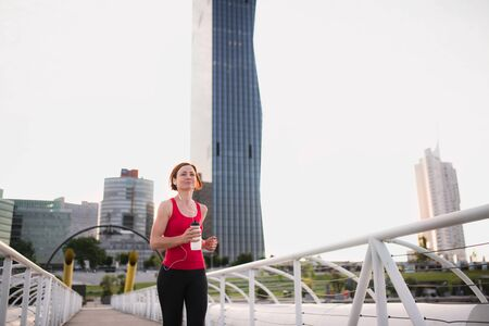 Front view of young woman runner with earphones jogging in city.