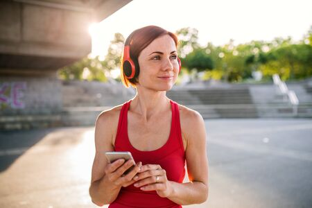 Young woman runner with headphones in city, using smartphone.