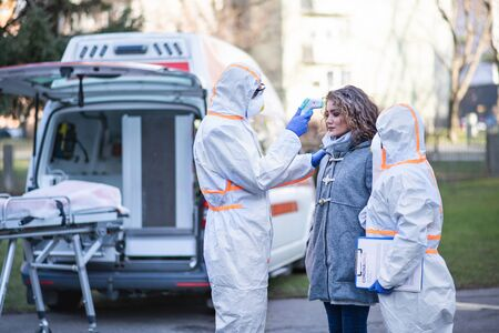 People with protective suits helping woman outdoors, coronavirus concept. Stockfoto