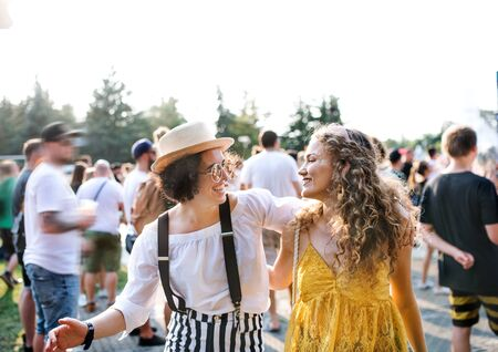 Two young women friends walking at summer festival. Stock fotó