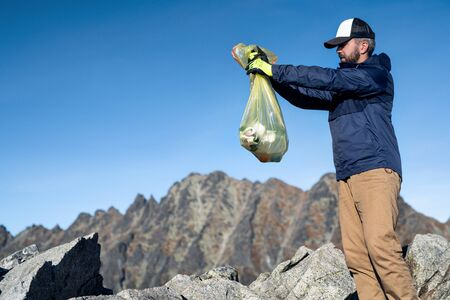 Mature man hiker picking up litter in nature in mountains, plogging concept.