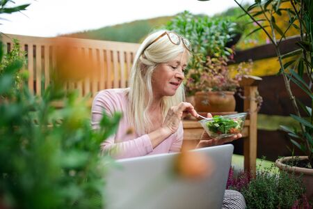 Senior woman with laptop sitting outdoors on terrace, eating lunch.