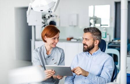Man and dentist with tablet in dental surgery, annual check-up.