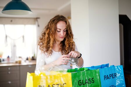 Young woman indoors at home separating glass, paper, and plastic waste.