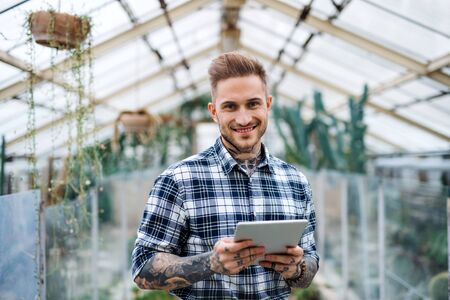 Man researcher standing in greenhouse, using tablet.