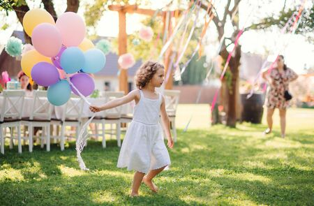 Portrait of small girl playing with balloons outdoors on garden party in summer.