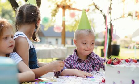 Down syndrome child with friends on birthday party outdoors in garden. Stockfoto