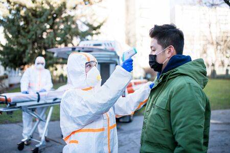 People with protective suits helping man outdoors, coronavirus concept. Stockfoto