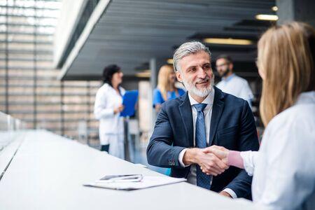 Doctors talking to pharmaceutical sales representative, shaking hands.