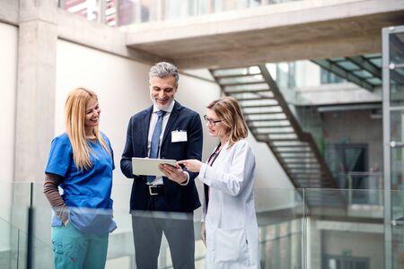Gruppo di medici che parlano con rappresentante farmaceutico.
