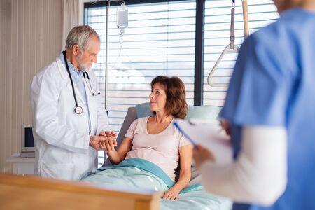 Doctor and nurse examining senior patient in bed in hospital. Banco de Imagens