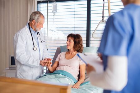 Médecin et infirmière examinant un patient âgé au lit à l'hôpital. Banque d'images