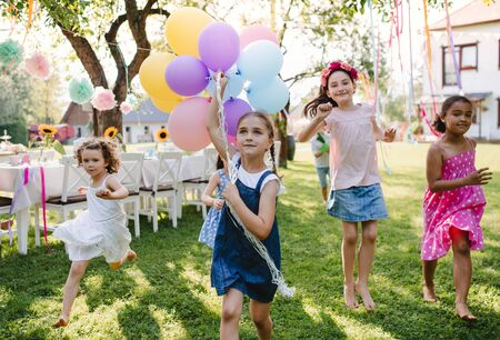 Small children outdoors in garden in summer, playing with balloons.