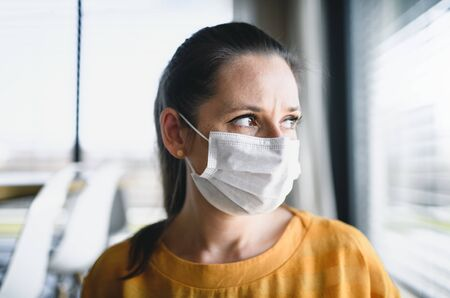 Woman with face masks indoors at home, Corona virus and quarantine concept.