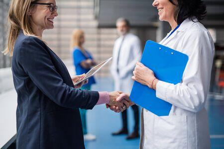 Doctor talking to pharmaceutical sales representative, shaking hands. Archivio Fotografico