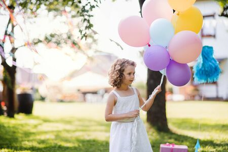 Small girl outdoors in garden in summer, playing with balloons.