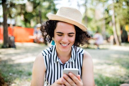Young woman at summer festival or camping holiday, using smartphone. Stock fotó
