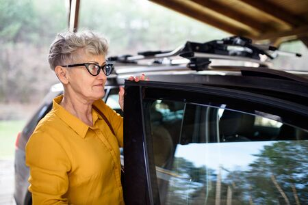 Senior woman with glasses standing outdoors by car by house.