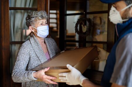 Courier with face mask delivering parcel to senior woman, corona virus and quarantine concept.