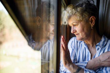 Sad senior woman standing indoors at home, corona virus and quarantine concept. Foto de archivo