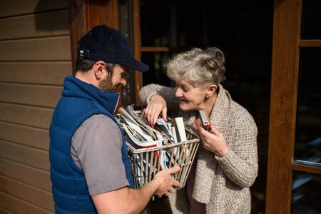 Man courier delivering books and magazines to senior woman. Stock Photo