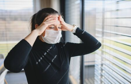 Woman with headache and face masks indoors at home, Corona virus concept.