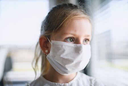 Piccola ragazza con maschere facciali in casa, virus Corona e concetto di quarantena.