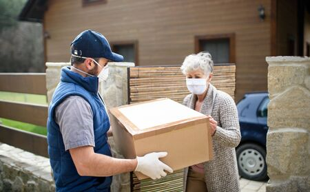 Courier delivering parcel to senior woman with face mask, corona virus and quarantine concept.