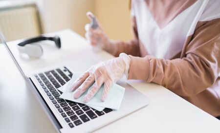 Unrecognizable young student with gloves at the table, disinfecting laptop.