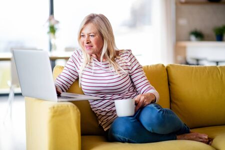 Senior woman with coffee and laptop indoors at home, relaxing.