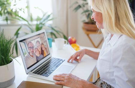 Senior woman with laptop indoors at home, family video call concept.