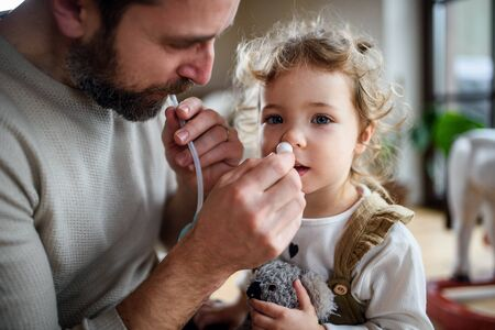 Father with small sick daughter indoors at home, using nasal aspirator. Stockfoto
