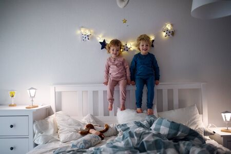 Two small children playing on bed indoors at home, having fun.